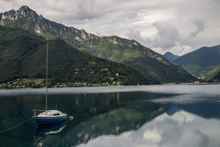 Sailboats moored on lake against mountains