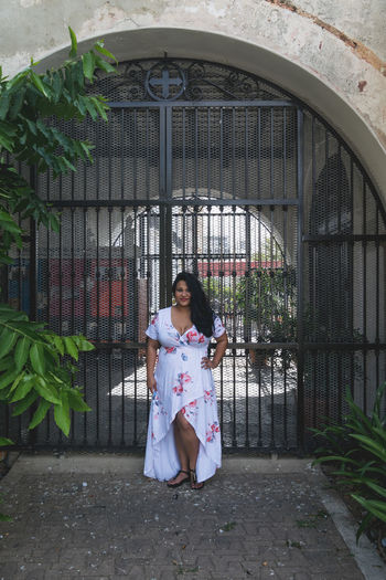 Woman Standing Against Metal Gate