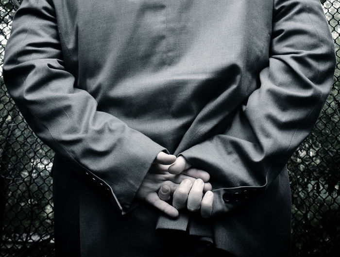 Business Businessman Close-up Focus On Foreground Grey Grey Suit Hands Behind Back Holding Person Suit