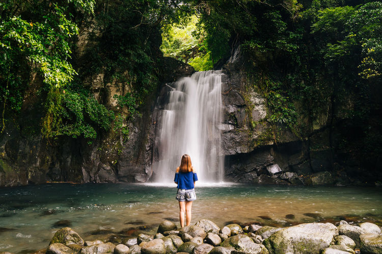 Rear view of woman looking at waterfall while standing on rocks