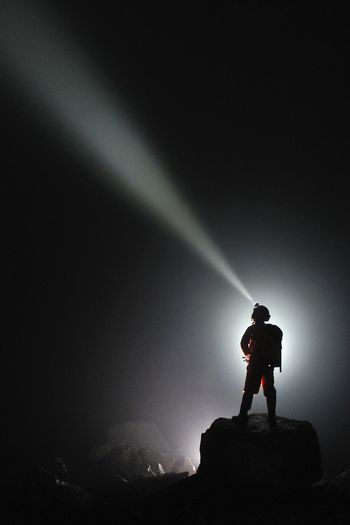 Man using flashlight while standing on rock at night