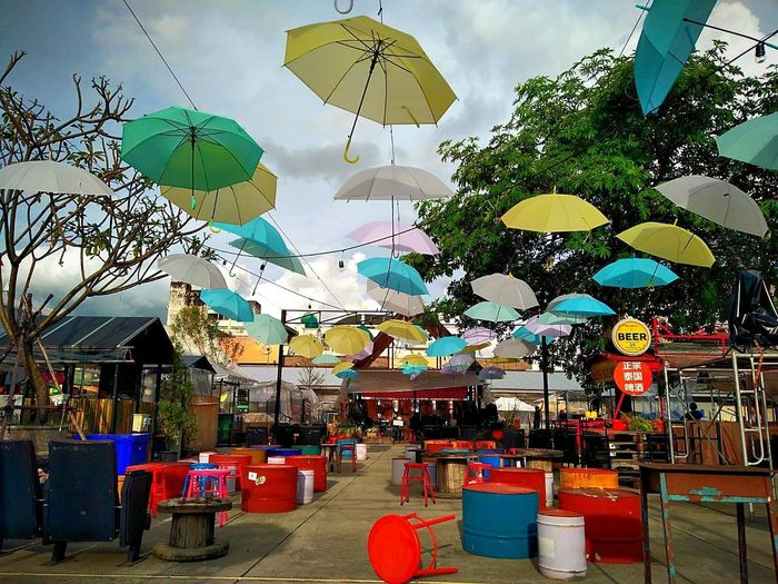 Hanging Built Structure Day Tree Multi Colored Outdoors Architecture Sky No People Building Exterior City Market Umbrellas Umbrellas In The Sky Colors Colorful Tables And Chairs Empty Places