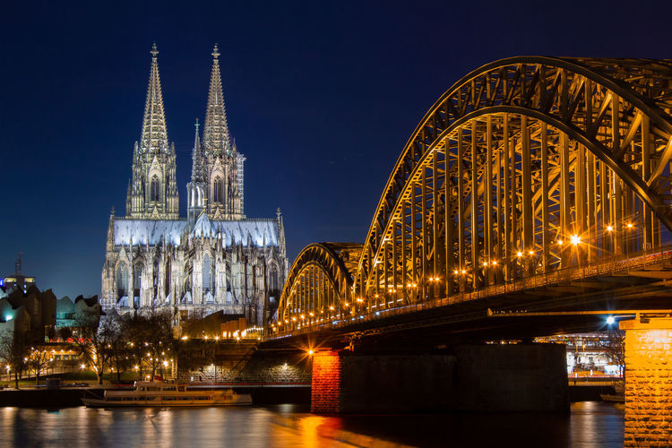 Cologne skyline with Cologne Cathedral and Hohenzollern bridge at night Cologne Cologne Cathedral Cathedral Architecture Built Structure Building Exterior Night Illuminated Bridge Travel Destinations Bridge - Man Made Structure Water Connection Sky River City Religion Tourism Place Of Worship Travel No People Arch Outdoors Spire  Skyscraper Arch Bridge