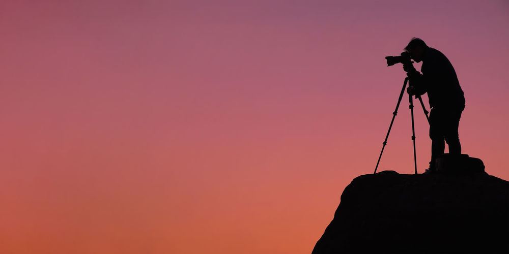 Silhouette man standing on rock against sky during sunset