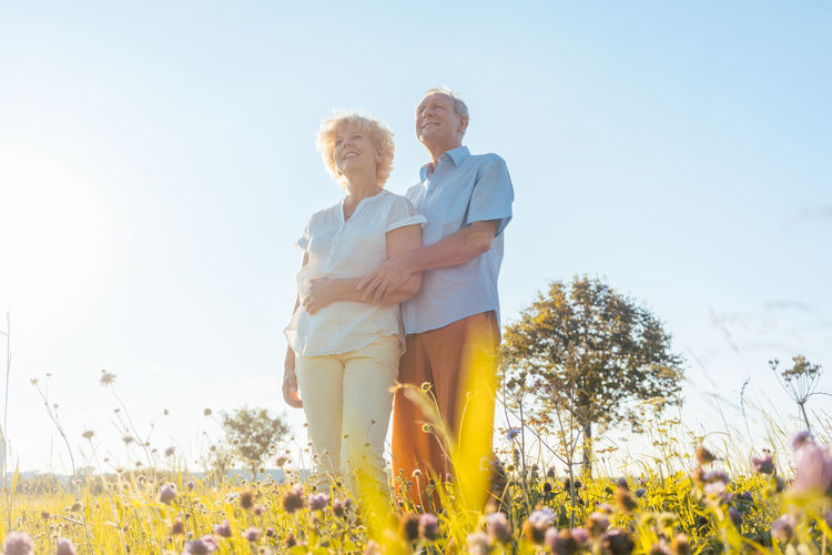Low angle view of smiling senior couple looking away while standing on field against sky during sunny day