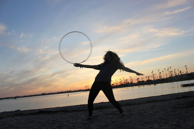 Full Length Of Woman Dancing With Plastic Hoop At Beach During Sunset