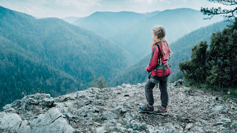 Young girl wearing mountain climbing harness standing on a rocky cliff and looking on a distant hills Adventure Backpack Beauty In Nature Blond Hair Day Hiking Leisure Activity Lifestyles Mountain Mountain Range Nature One Person Outdoors People Real People Scenics Sky Standing Tree