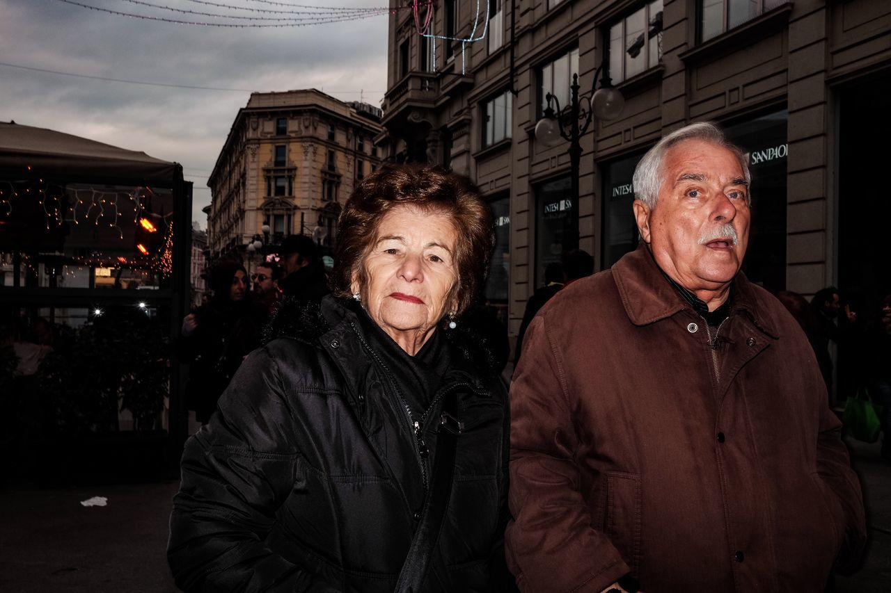 architecture, two people, building exterior, built structure, senior adult, real people, street, senior men, night, outdoors, city, looking at camera, men, lifestyles, togetherness, women, portrait, sky, people