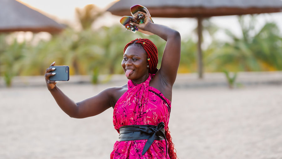 Woman photographing with mobile phone outdoors