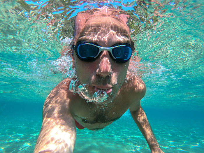 Portrait of shirtless man swimming in sea