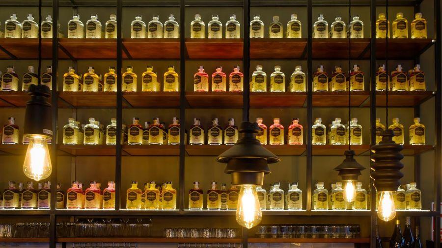 Bottles arranged on shelves in illuminated bar