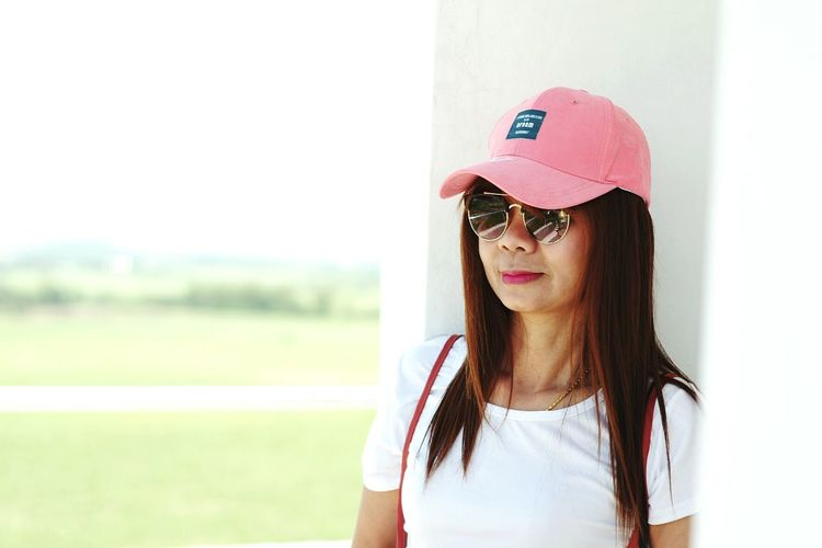 Woman Wearing Sunglasses And Cap By Wall