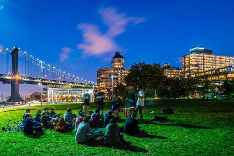 People sitting in park by bridge and illuminated buildings against blue sky at dusk