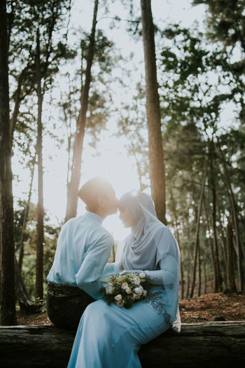 Rear view of couple sitting in forest