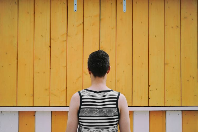 Rear view of man standing against yellow wooden wall
