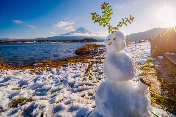 Snowman By Lake Kawaguchi With Mt Fuji In Background Against Sky On Sunny Day During Winter