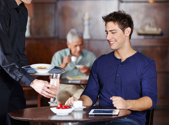 Young man holding ice cream in restaurant