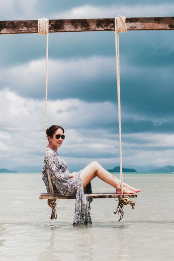 Full length portrait of young woman on beach against sky