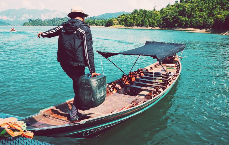 Nautical Vessel Water Transportation Day Mode Of Transport Outdoors Men Moored Standing Full Length Nature Real People Fisherman One Person Sea Tree Longtail Boat Beauty In Nature One Man Only Only Men