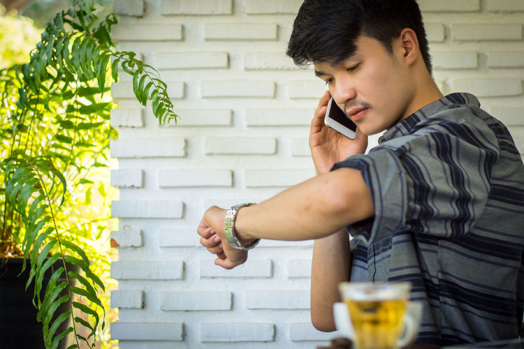 Side View Of Young Man Checking Time While Talking On Phone At Cafe