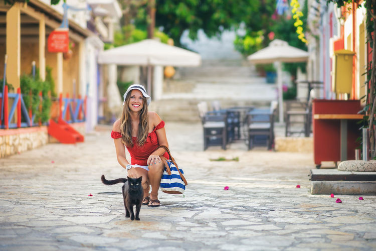 Young woman with her cat Beauty Brunette Building Exterior Cat Caucasian Cute Domestic Animals Fashion Fiscardo Girl Greece Happiness Kitty Lifestyles Looking At Camera Nice Outdoors People Pets Portrait Smiling Street Summer Women Young Adult The Portraitist - 2017 EyeEm Awards Live For The Story EyeEmNewHere Sommergefühle EyeEm Selects
