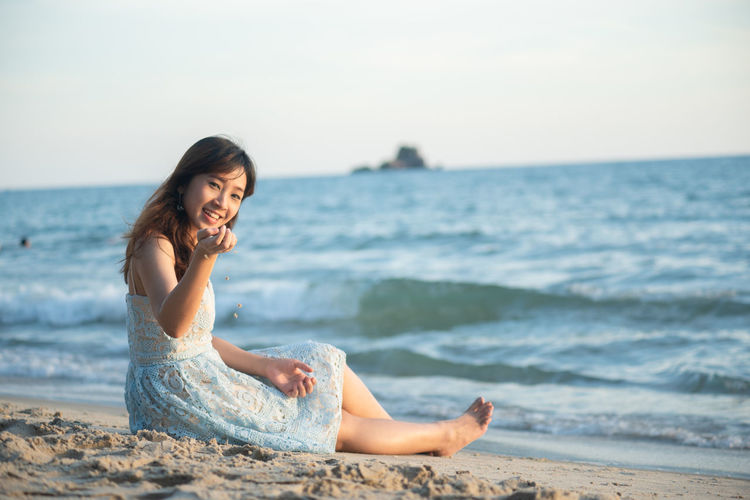 Young woman sitting on shore at beach against sky