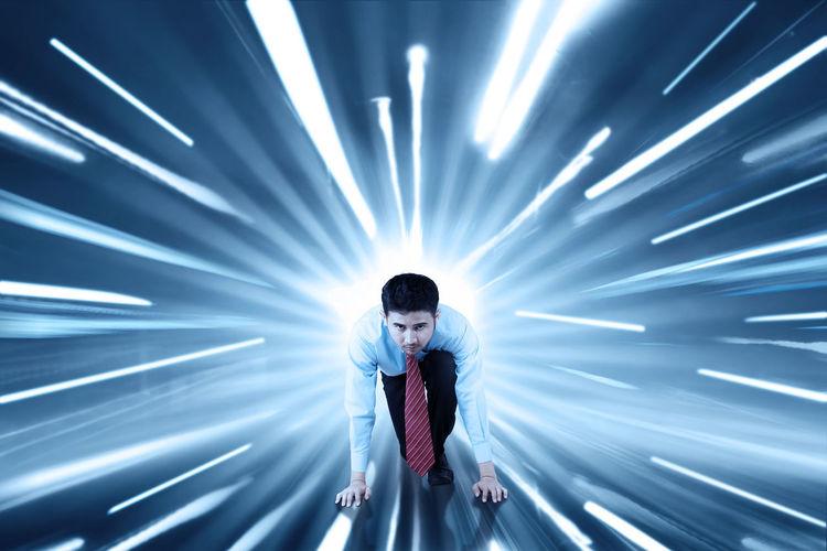 Full length of man standing against illuminated light