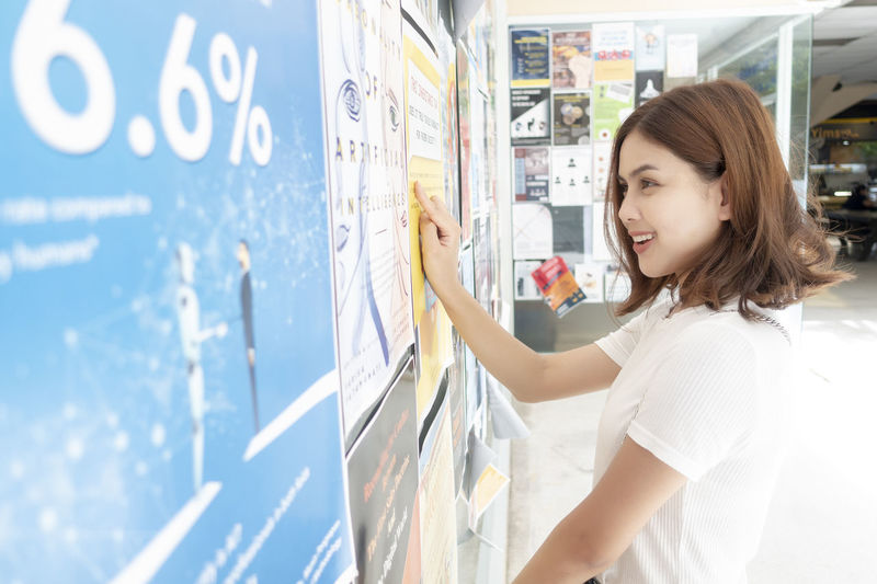 Smiling young woman standing by bulletin board
