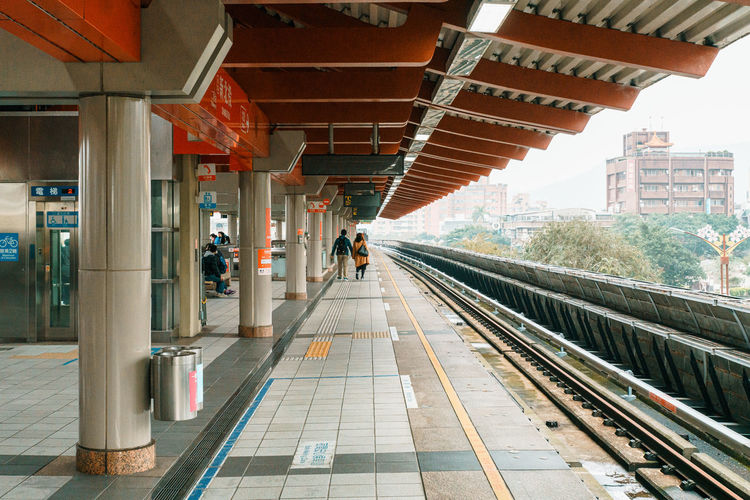 Rear view of couple walking on railroad station platform