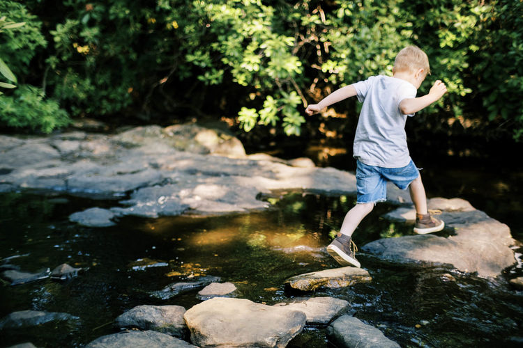 Rear view of boy standing on rock by stream