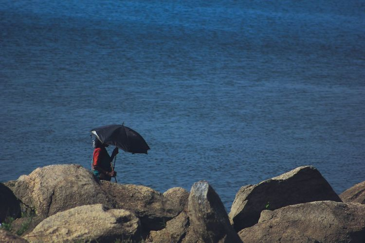 High Angle View Of Woman With Umbrella Standing At Rocky Beach