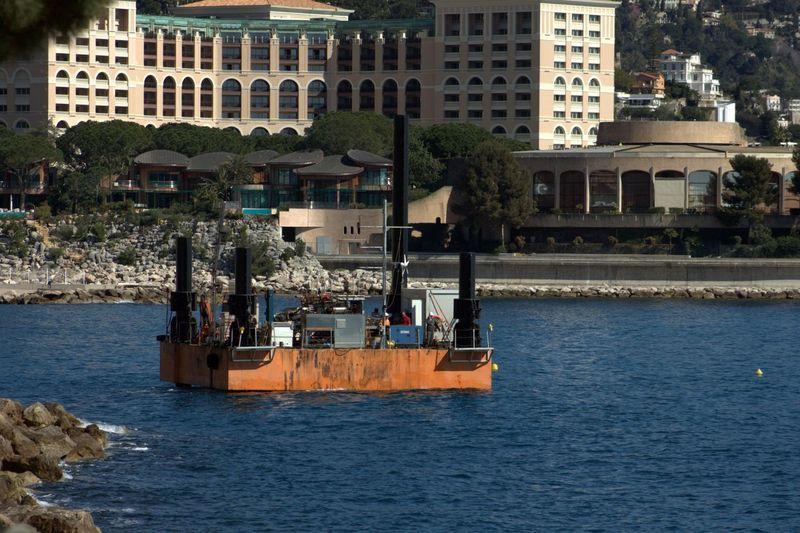 Oil Drilling Platform In Sea Against Residential Building