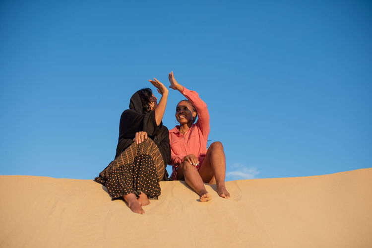 People on sand dune against clear blue sky