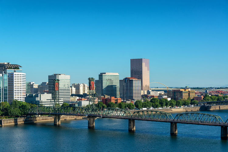 Cityscape view of wonderful downtown Portland, Oregon with the Hawthorne Bridge in the foreground Portland Oregon No People Outdoors Cityscape Travel Tourism Travel Destinations Building Exterior Built Structure Architecture Sky City Building Nature Office Building Exterior Skyscraper Pacific Northwest  Northwest Willamette River  River Blue Sky Skyline Urban Skyline Urban United States USA Bridge Bridge - Man Made Structure Hawthorne Bridge Water Blue Clear Sky Connection Copy Space Waterfront Tall - High Modern Financial District
