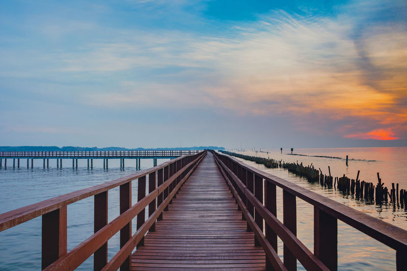 Old wood bridge in to sky. Sky Water Wood - Material Sea Cloud - Sky Beauty In Nature Scenics - Nature Tranquil Scene Pier Tranquility Direction The Way Forward Railing Nature Horizon Over Water Built Structure Sunset Architecture Horizon No People Diminishing Perspective Outdoors Wood Paneling Long Wood