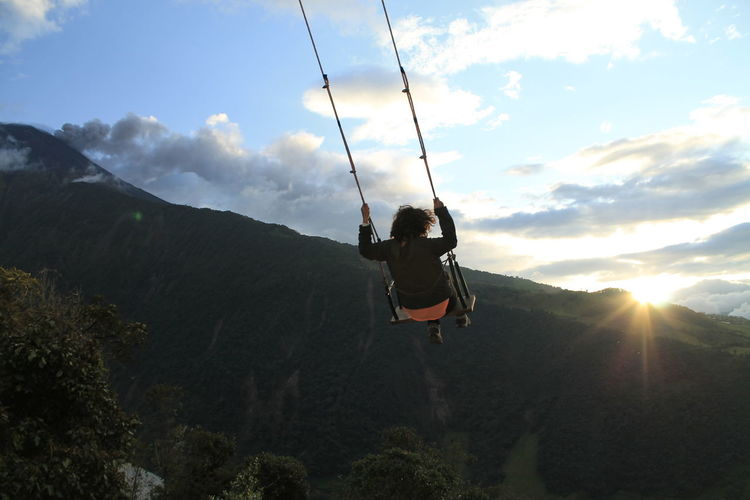 swinging at the end of the world in the sunset Adult Adventure Beauty In Nature Day Landscape Leisure Activity Mountain Nature One Person Outdoors People Sky Sport Swing Tree Vitality Young Adult