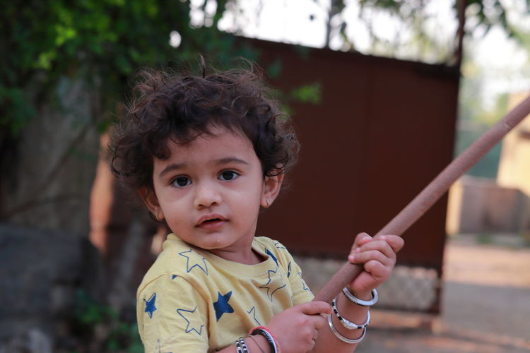An indian little child looking at the camera holding a wooden stick