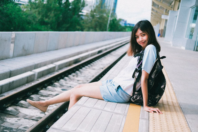 Portrait of smiling young woman sitting on railroad track