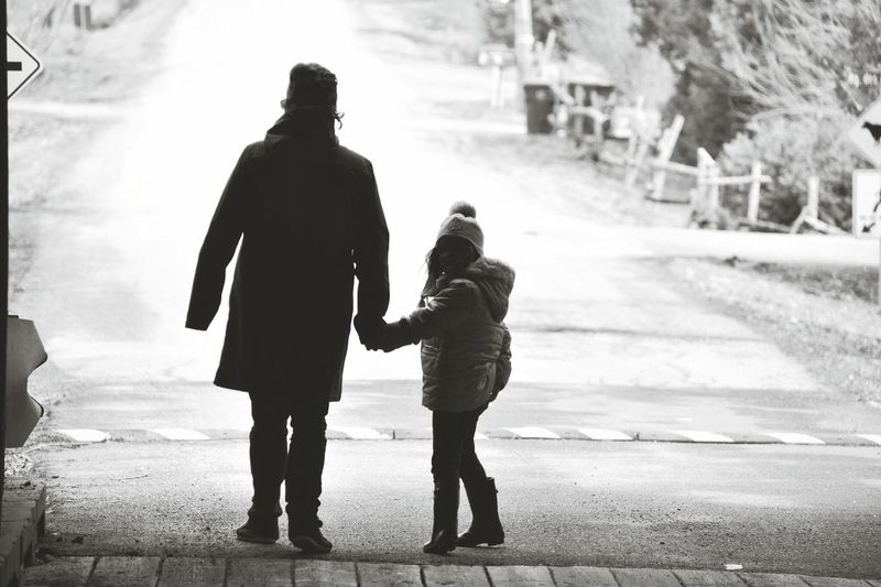 Father And Daughter Holding Hands While Walking On Road