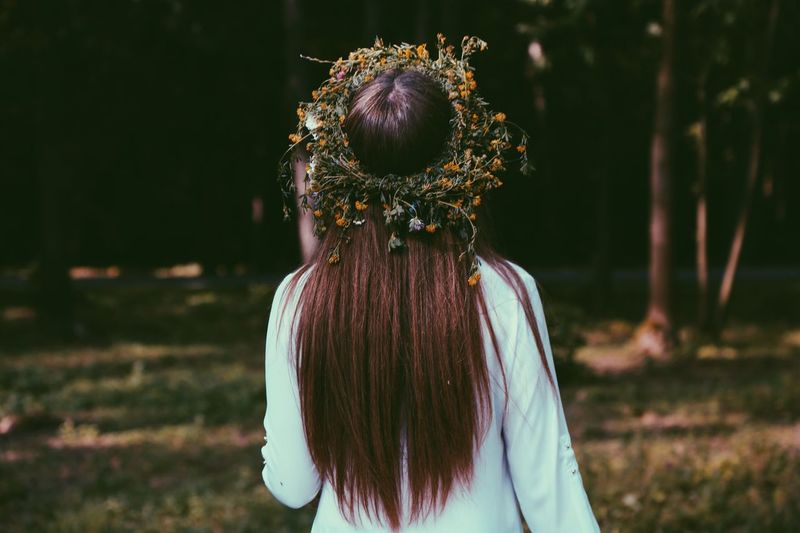 Rear View Of Woman Wearing Wreath In Forest