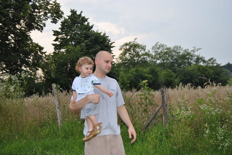 Bald Father Carrying Cute Son While Standing On Field