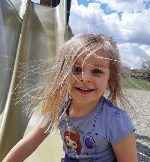 Portrait of cute smiling girl with messy hair outdoors