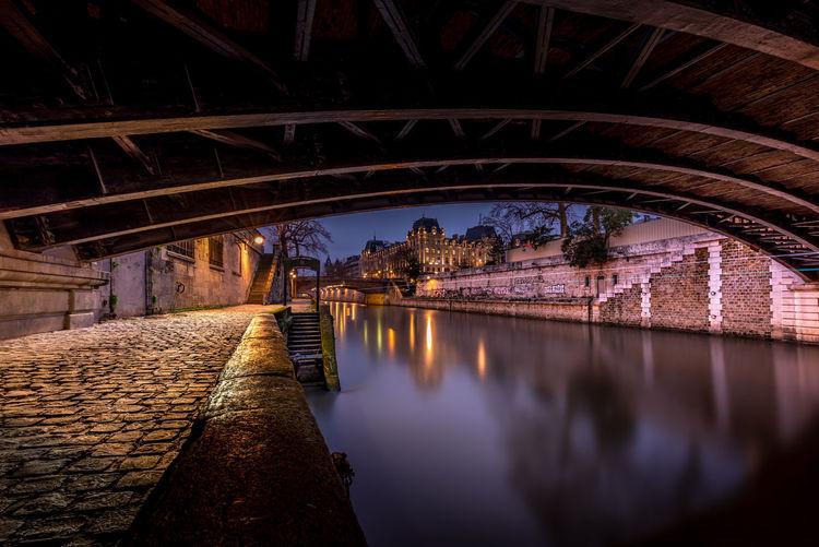 Arch bridge over river at night in paris