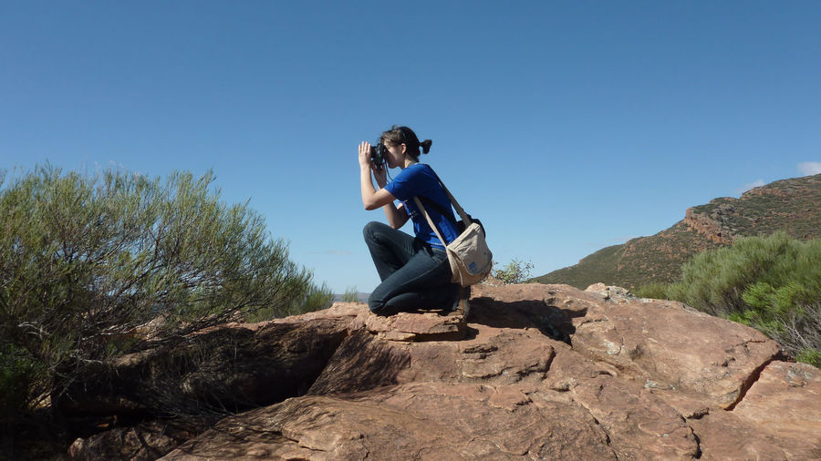 Woman Photographing Through Camera While Kneeling On Rock Against Clear Sky