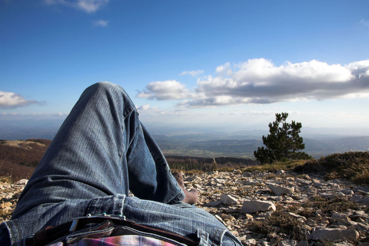 Low section of man relaxing against landscape
