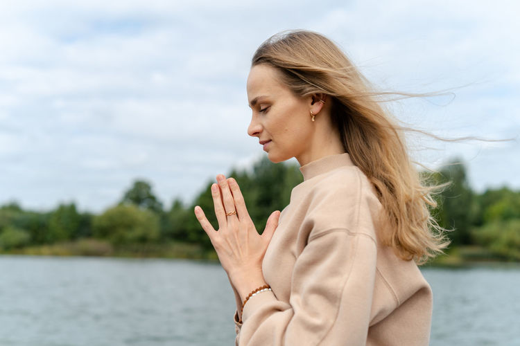 Beautiful woman standing by water against sky