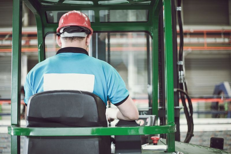 Rear view of man sitting in forklift in factory