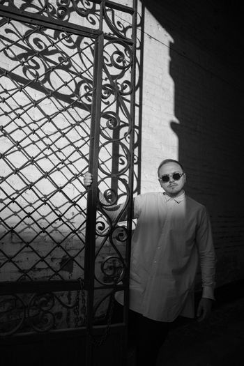 Man wearing sunglasses standing against built structure