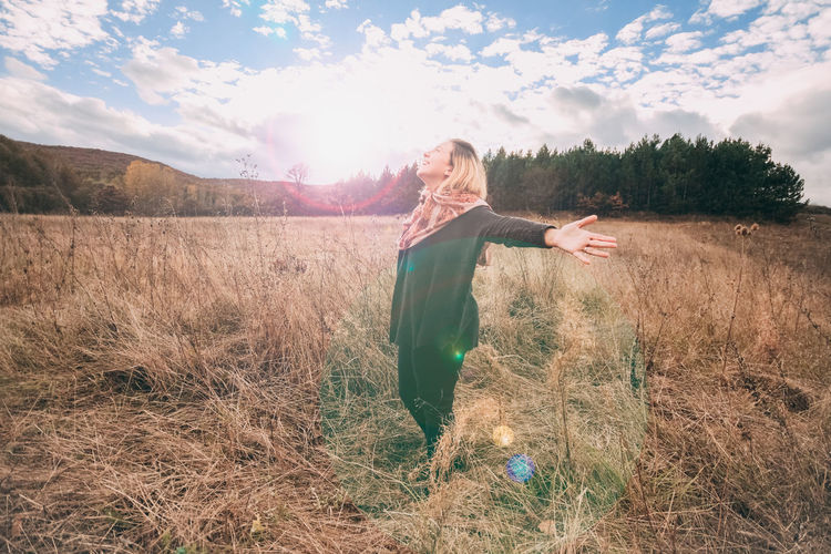 Young Woman With Arms Outstretched Standing On Field Against Sky