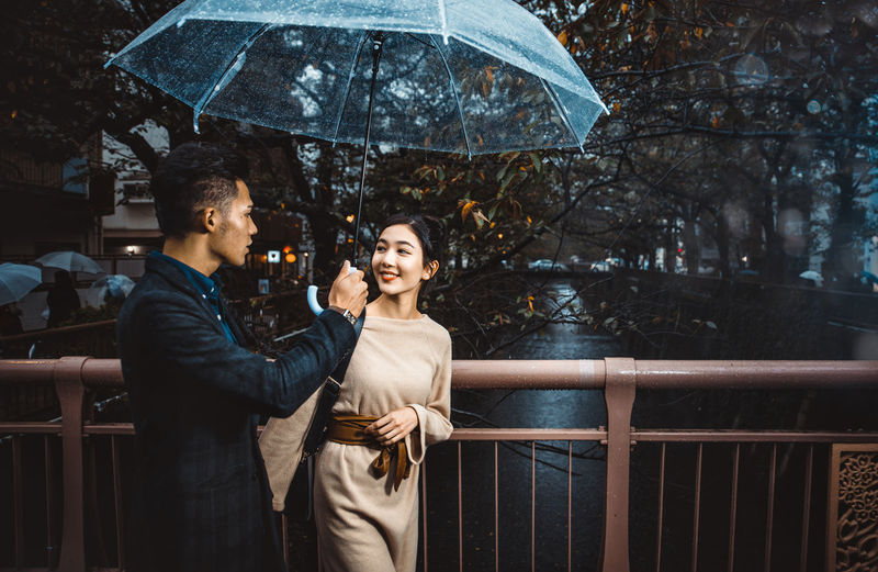 Young couple standing on railing during rain